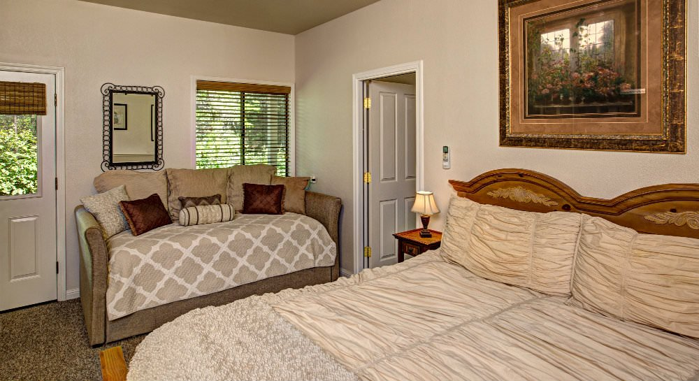Bedroom with wood headboard and ivory comforter, upholstered love seat with tan and brown pillows, glass door and window