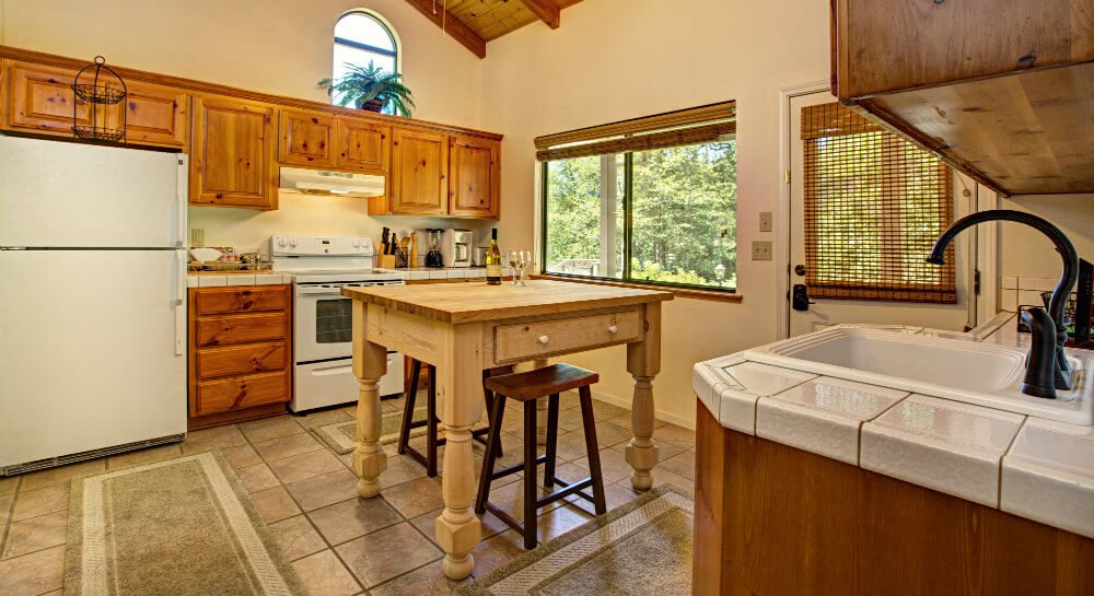 kitchen with white refrigerator, stove, light wood cabinets on back wall, square butcher block island in center, sink and white tile counter on right