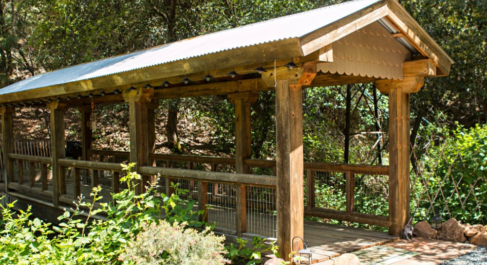 wooden covered pedestrian bridge with metal roof in wooded setting