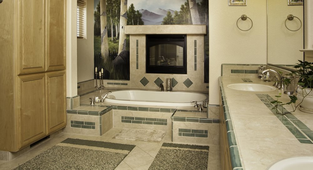 Bathroom with light wood armoire, beige tiled floors, oval tub surrounded by beige and sage green tile and scenic mural