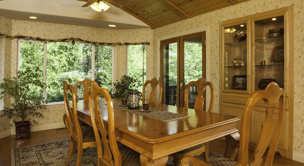 Vaulted dining room, wood dinette set, view of trees outside window, built-in cabinet with décor, double glass french doors