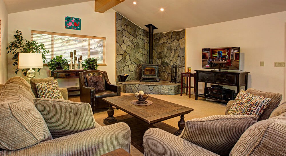 living room with vaulted ceiling, tan sofas and leather chair surrounding wood coffee table, corner wood stove with fieldstone on walls, tv on dark wood sideboard