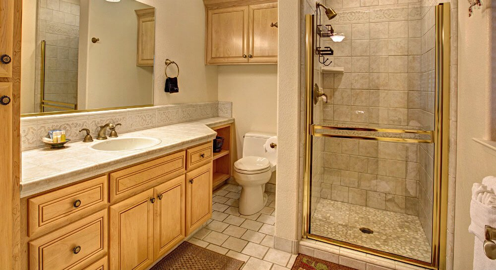 bathroom with light wood cabinets, sink with large mirror, shower with stone tile walls, glass door with shiny gold trim