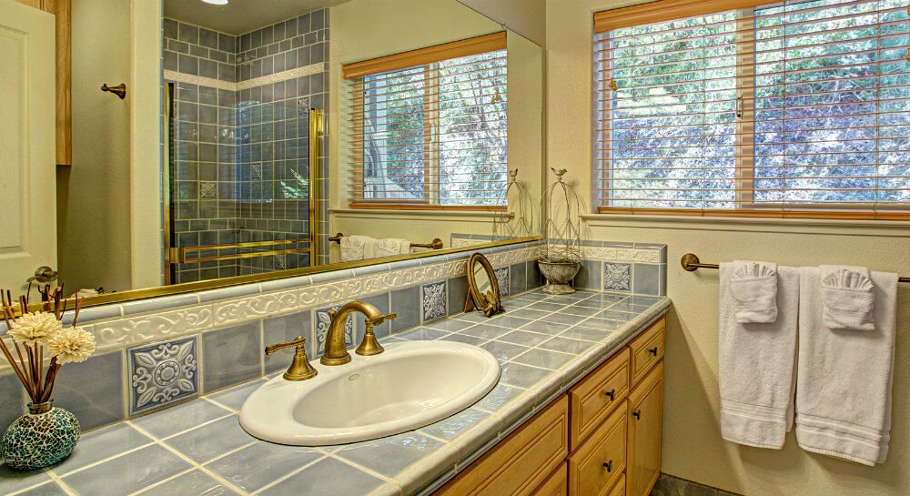 bathroom sink set in light blue tile counter and light wood cabinetry, long mirror reflecting glass door shower