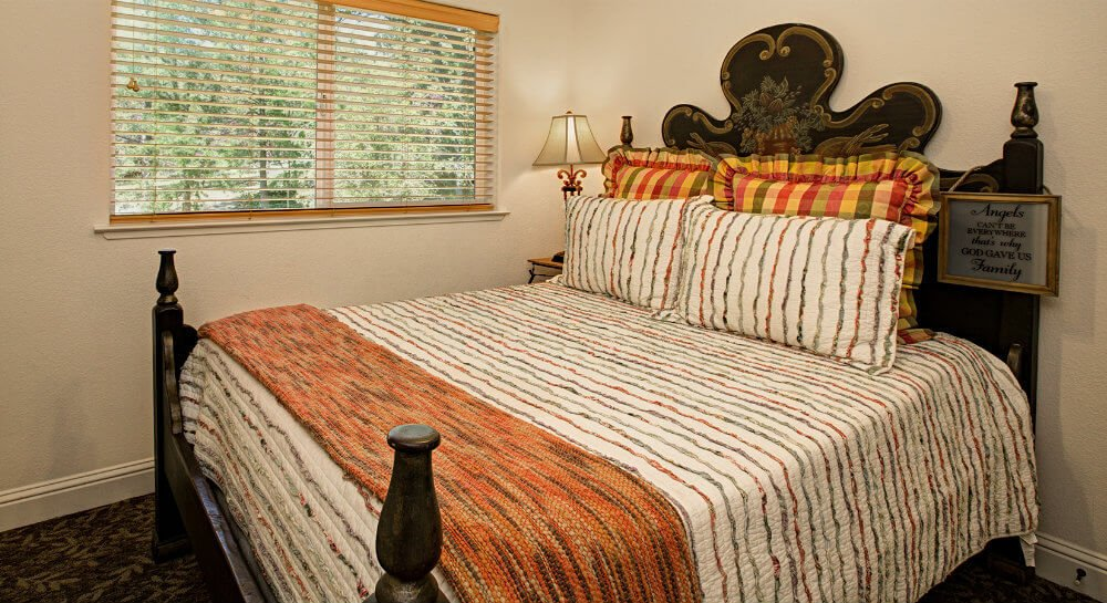 bed with dark decorative headboard, white, orange and green striped linens and pillows