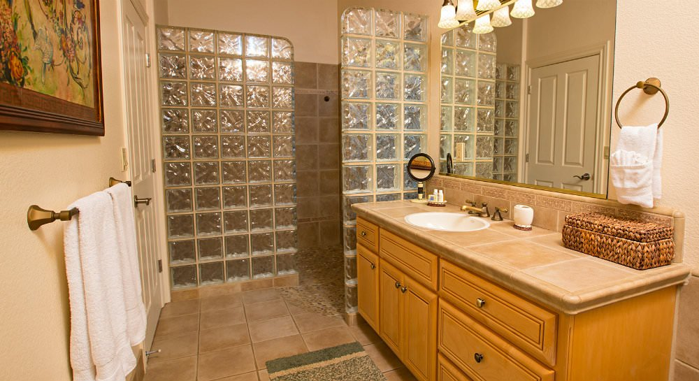 Beige bathroom with tiled floors, wood vanity with tiled top and large tiled walk-in shower with privacy glass walls