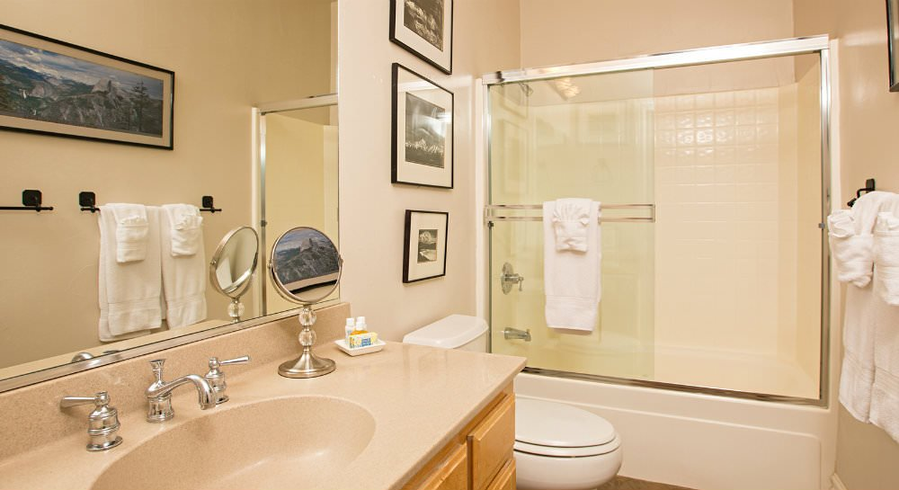 Bathroom with tub shower surround and glass doors, framed black and white prints, beige vanity, large mirror and white towels
