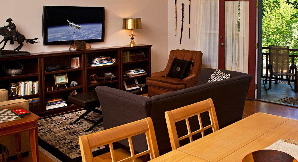 Living area with hardwood floors, black tan and ivory rug, sofa and two chairs, bookcases with books, décor and TV