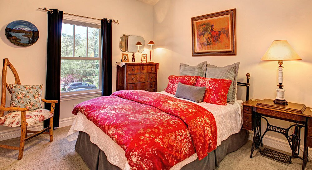 bed with deep red floral cover, grey pillows and accent linens, sewing machine table with lamp, unique wood tree-limb chair