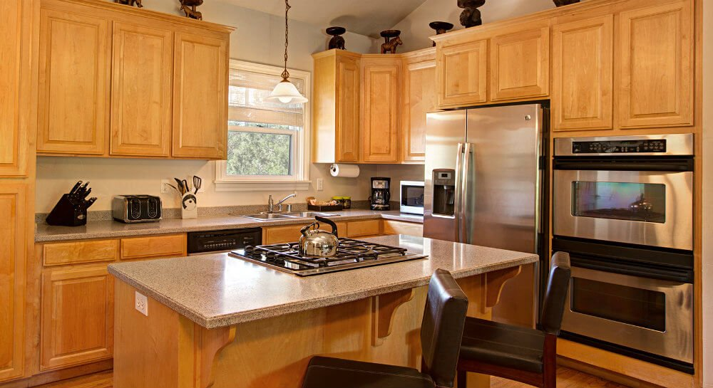 kitchen with light wood cabinets, grey counters, stainless steel refrigerator and double oven, island with cooktop and two black leather stools