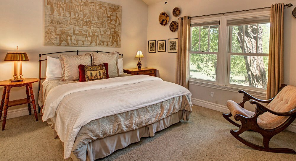 bed with iron headboard, light grey and white linens, side tables with lamps, rocking chair, large Egyptian print art on wall above bed