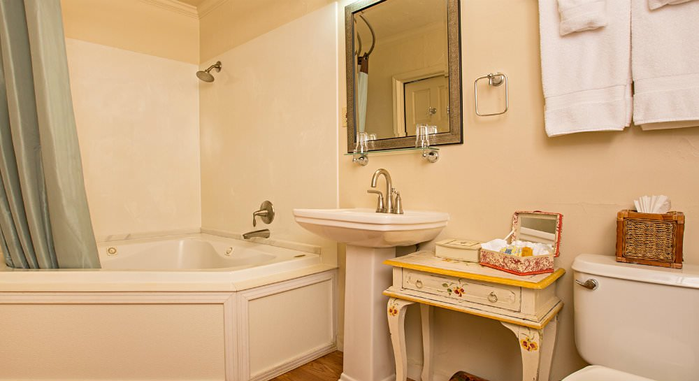 Ivory bathroom with corner tub, metal framed mirror over white pedestal sink and painted table with open box of toiletries