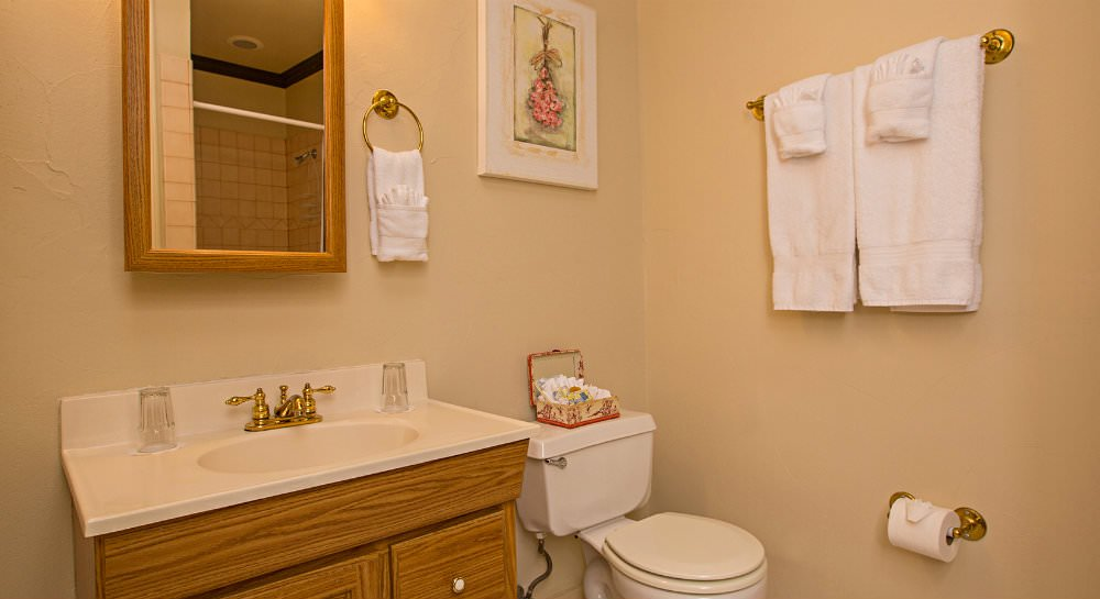 Ivory bathroom with wood vanity, white sink top with brass faucet, wood framed mirror, white towels hanging on towel bar