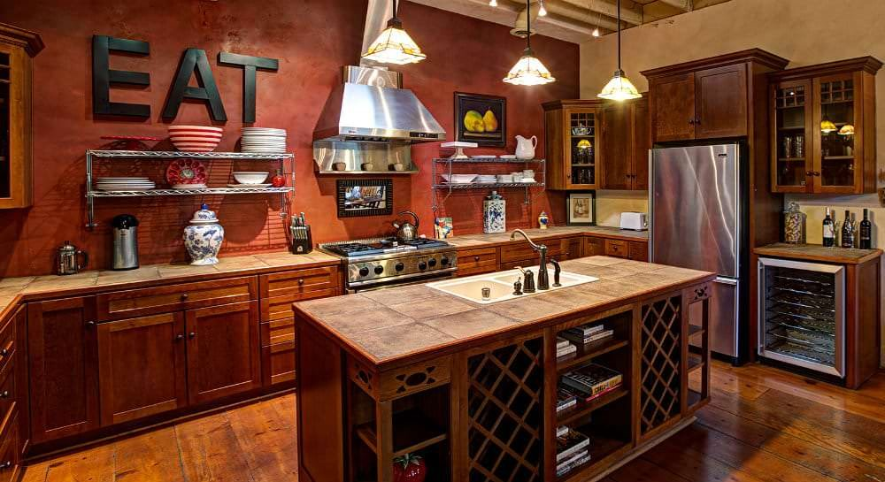 Kitchen with wood flooring, dark brown cabinets, stainless steel appliances, and light brown tile counters