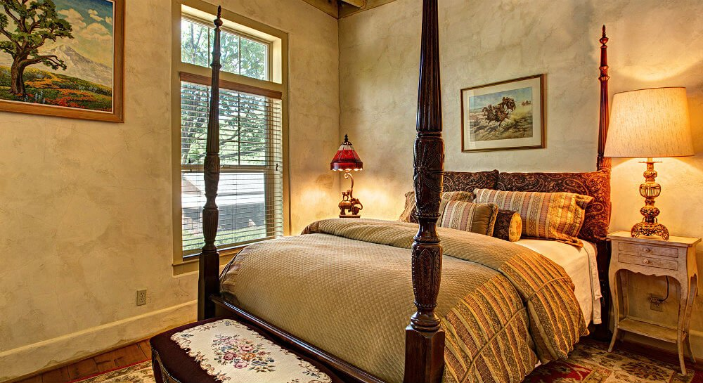 dark wood bed with tall posts, tan and red paisley linens, framed art on tan walls, bench at foot of bed with black and embroidered cover