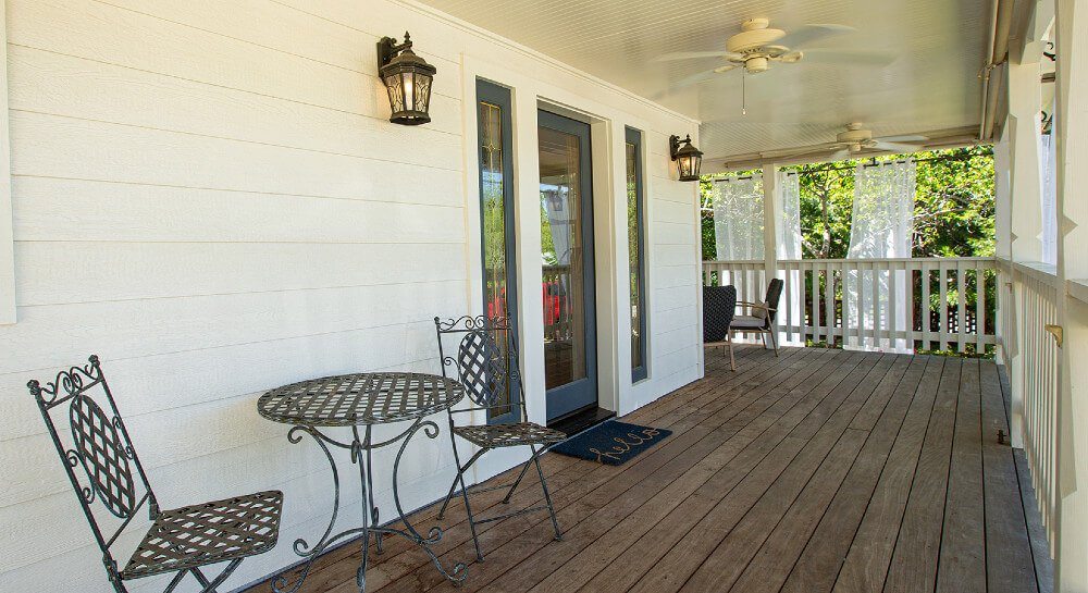 wooden wraparound porch starting in front of house with metal table and chairs and lawn furniture around corner