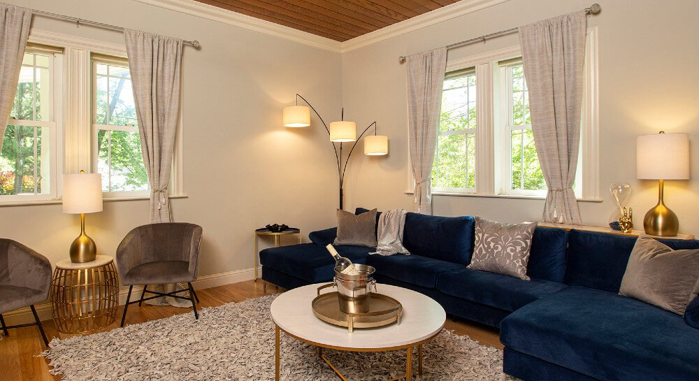 windows allowing ample light into living room with big blue velvet couch, furry floor cushion, round table with ice container holding holding wine bottle, table and floor lamps