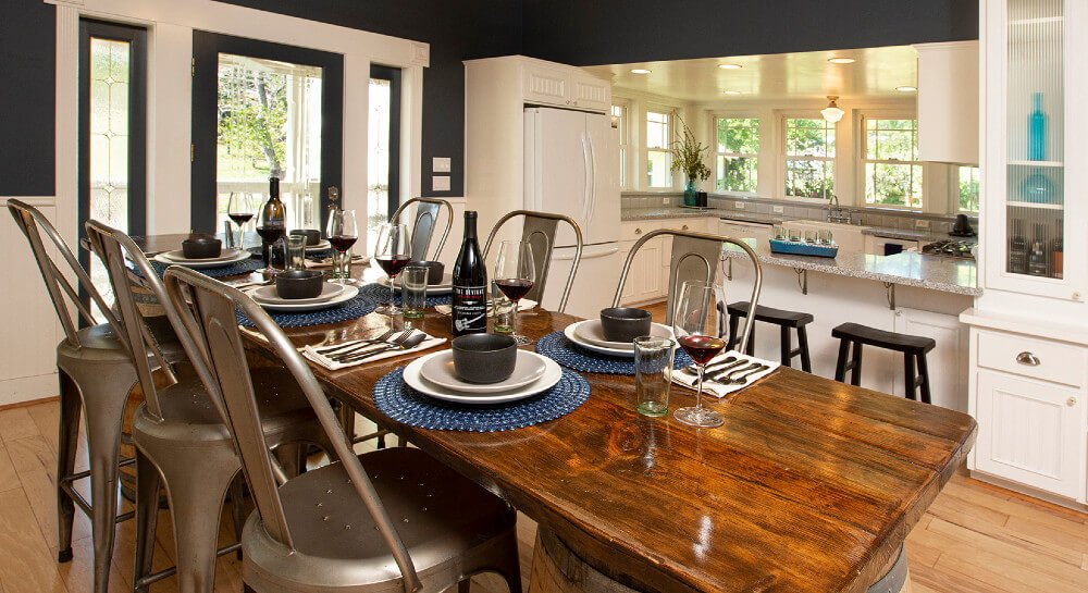 kitchen and dining rooms together with windows allowing in ample light, white appliances with wraparound counter space, white cabinets, view of garden from kitchen, wood flooring