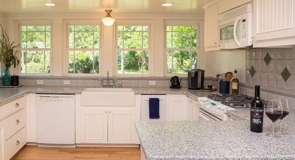 kitchen with white appliances (microwave, gas range, french door refrigerator), cabinets and wraparound gray granite countertop, view into woods through extensive windows