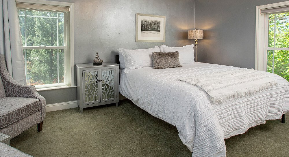 bedroom with gray walls with two windows with mini-blinds letting in much natural light, queen bed with white comforter and shams, floor lamp, brown chair