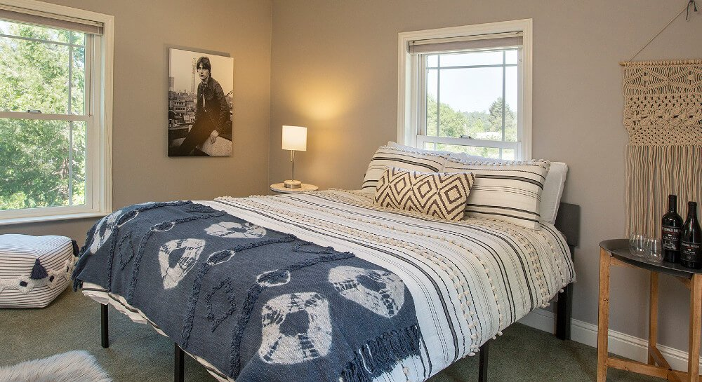bedroom with tan walls and carpet, queen bed with striped comforter, two windows with mini-blinds, square striped cushion