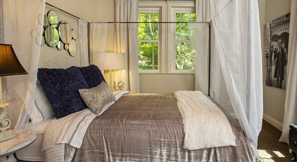 light yellow bedroom with a queen canopy bed with tan comforter, table lamps, two windows, black leather covered bench under window