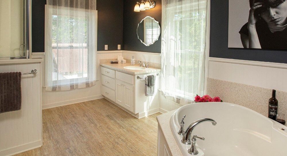 dark gray bathroom with wood laminate flooring, glass shower, separate tub, white vanity with sink inset in tan marble