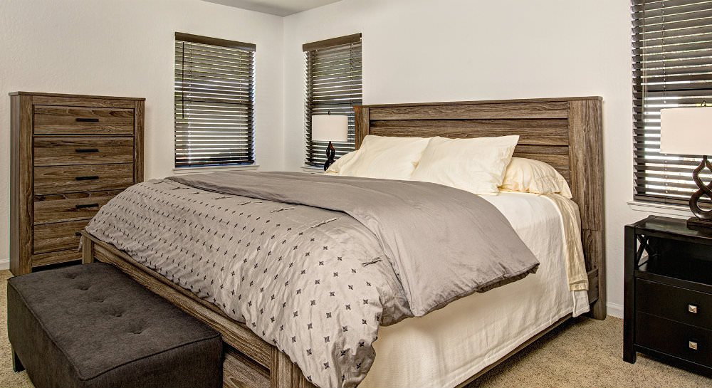 Bedroom with ivory walls, three windows, tan carpet, wood headboard and dresser, upholstered bench, ivory and tan blankets and pillows