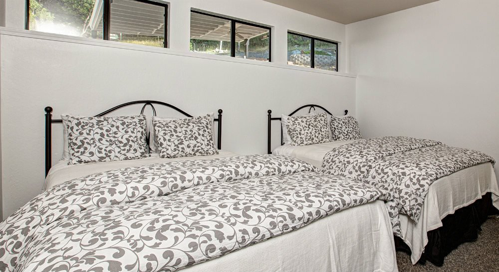 Bedroom with two beds, black metal headboards, ivory and grey blankets and pillows, and four small sliding glass windows