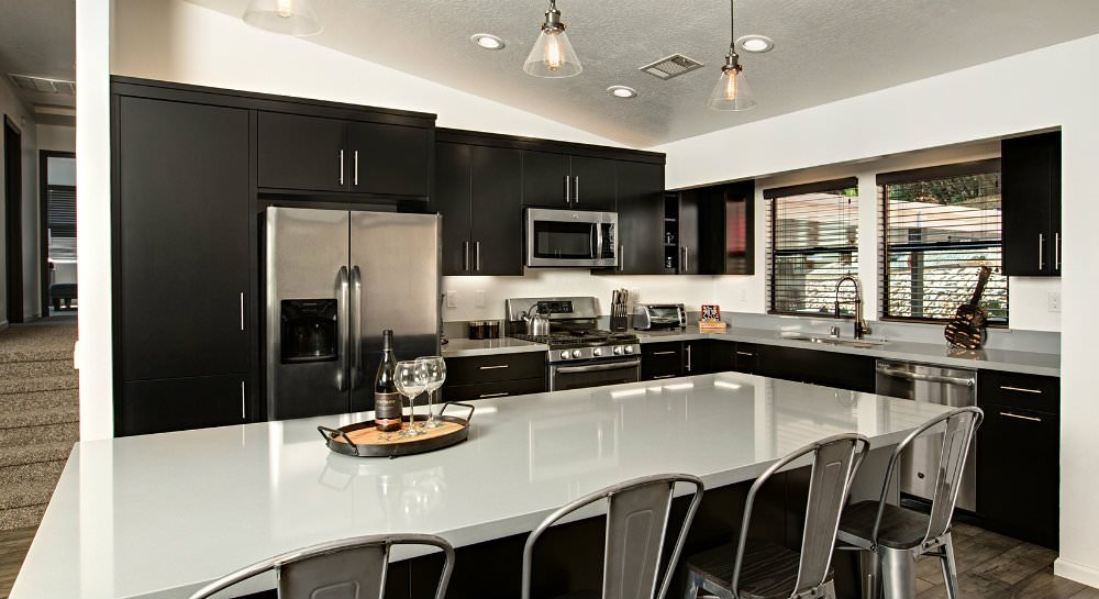 White vaulted kitchen with dark cabinetry, white shiny countertops, stainless steel appliances, island with four barstools, two windows over sink