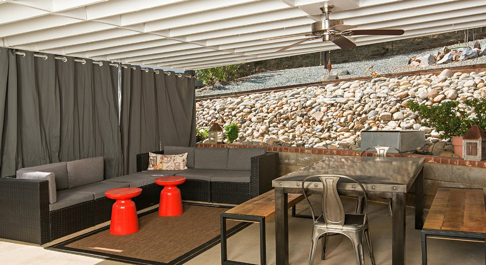 Covered patio with grey curtains, grey cushioned sectional, metal table with two bench seats and two chairs, and ceiling fan