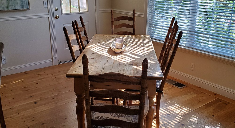 A breakfast nook with rustic wooden table and chairs stand in the sunlight peeking through windows.