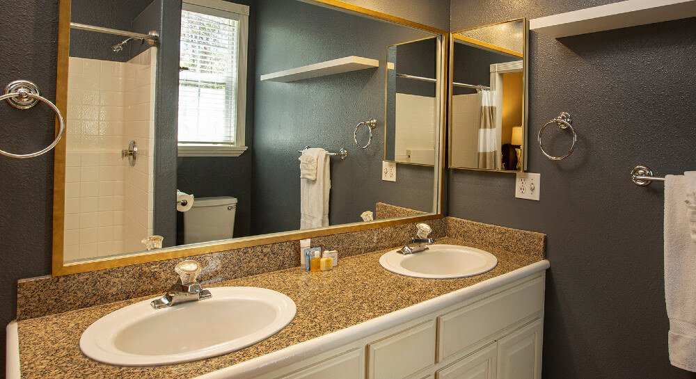 A bathroom with light over vanity mirror with side mirror and towel rack with white towels.