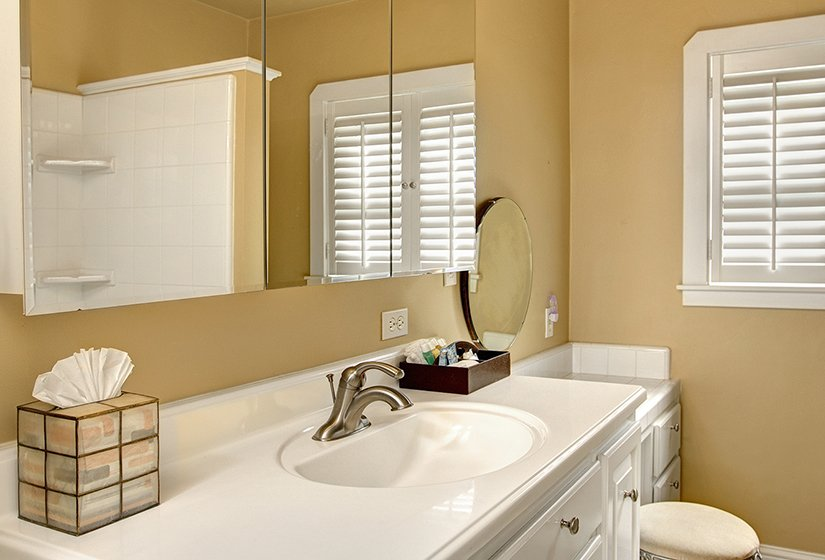 Tan walls, long white vanity/sink, mirror with reflection of tiled shower. Shuttered window over toilet.