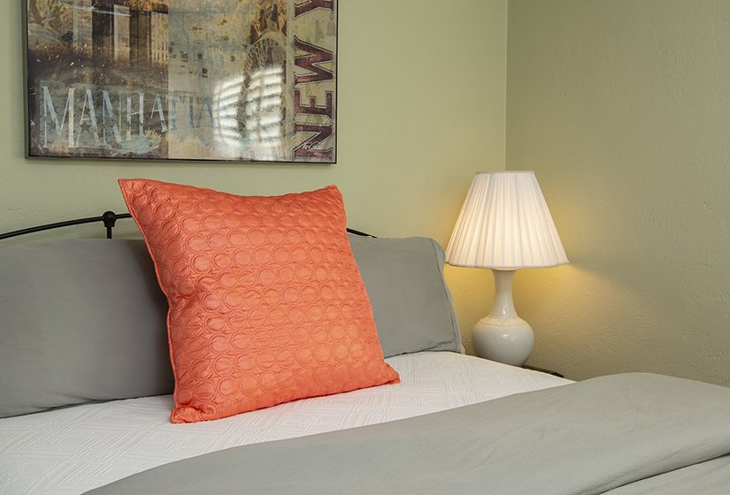 Olive walls with Manhattan framed print, nightstand with lamp, grey comforter and orange pillow on bed.