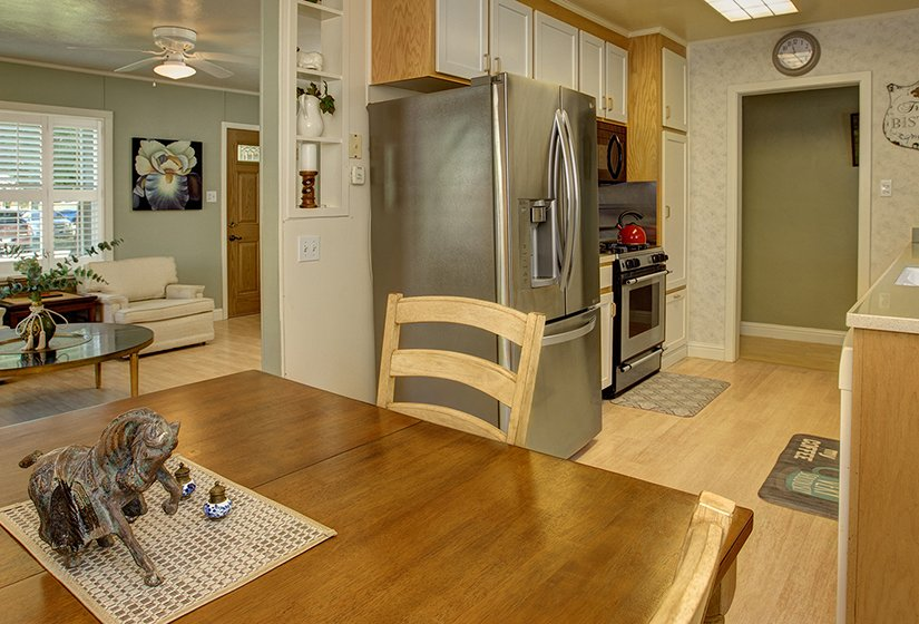 View from kitchen containing stainless steel appliances toward living room, wood table and chairs, yellow chairs living room, front door.