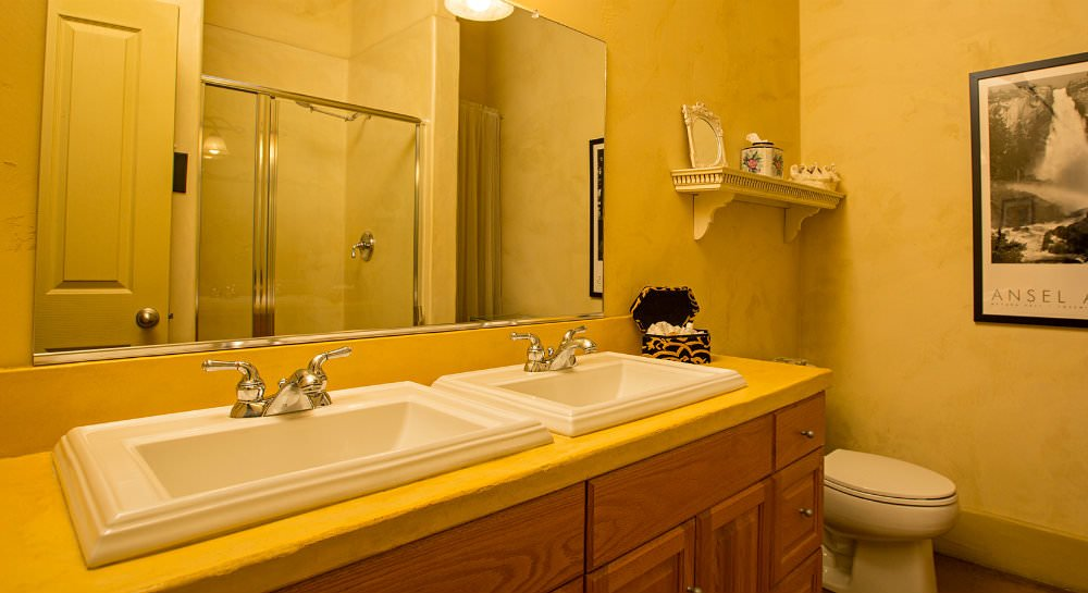 Yellow bathroom with wood vanity, double bowl sinks and large mirror, ivory decorative shelf on wall and framed photograph