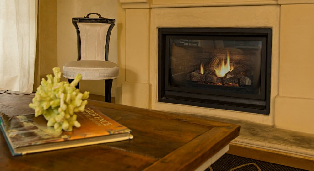 Close up of a wood plank coffee table topped with a book, a fireplace with warm fire and white chair