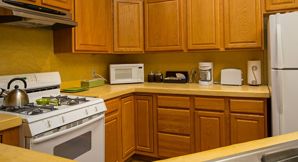 Yellow kitchen, light oak cabinetry, silver teapot on white stove, and microwave, toaster, coffee pot and coffee supplies on counter