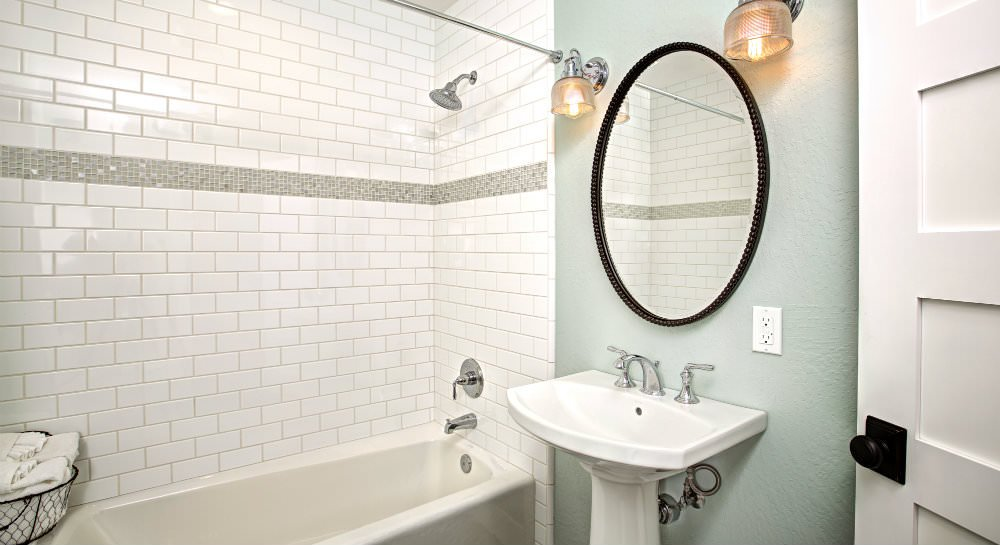 Bathroom with white subway tiled tub shower, white pedestal sink with bronze oval mirror, two sconce lights, and white towels