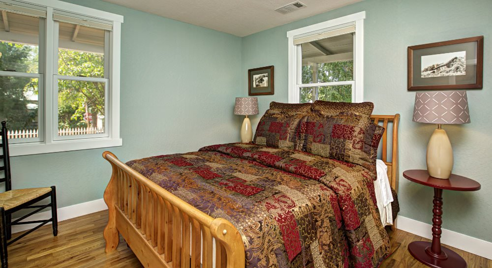 Aqua bedroom, white trim, hardwood floors, light wood sleigh bed, red, brown and gold comforter and pillows, nightstands with lamps