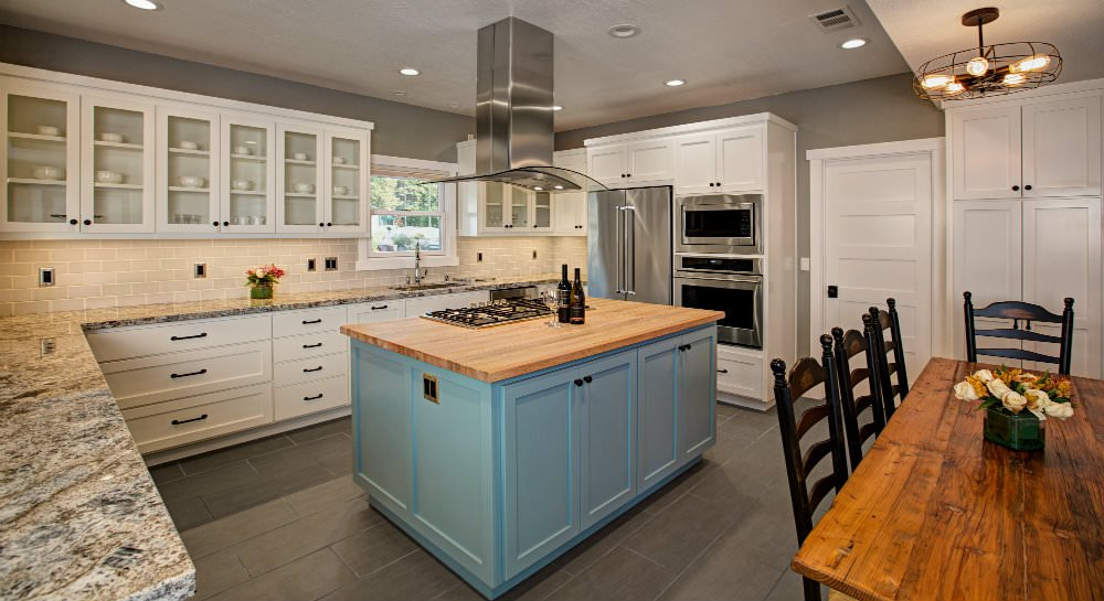 Large kitchen with white cabinetry, gray walls, stone countertops, tile backsplash, blue painted island with butcherblock top, stianless steel applicances