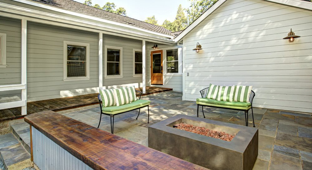 Slate patio with gas firepit, two benches with green and white cushions