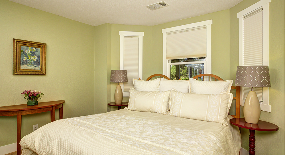 Soft green room with tall windows overlooking bed and antique furniture appointing the room.