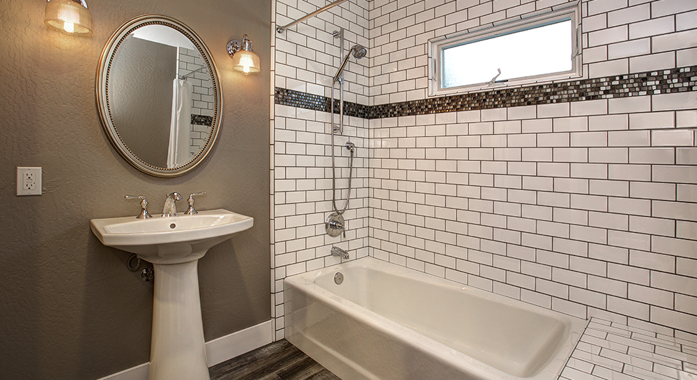 White tiled bathroom with wooden floors and pedestal sink underneath oval vanity mirror.