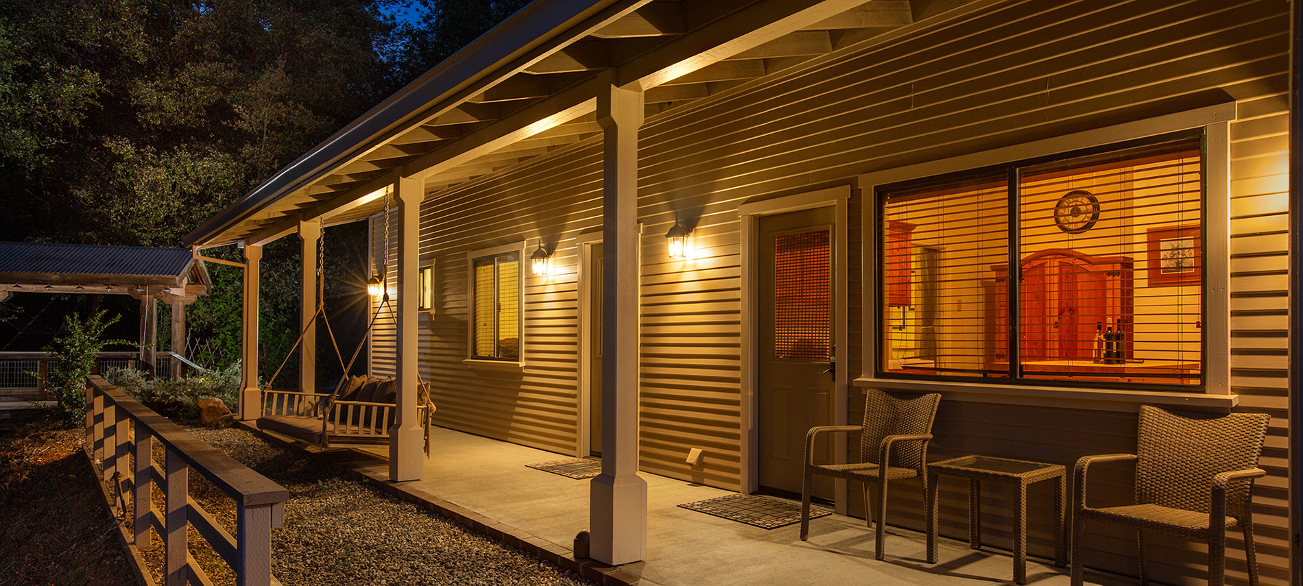 Exterior view of cabins at night, with kitchen visible through window.