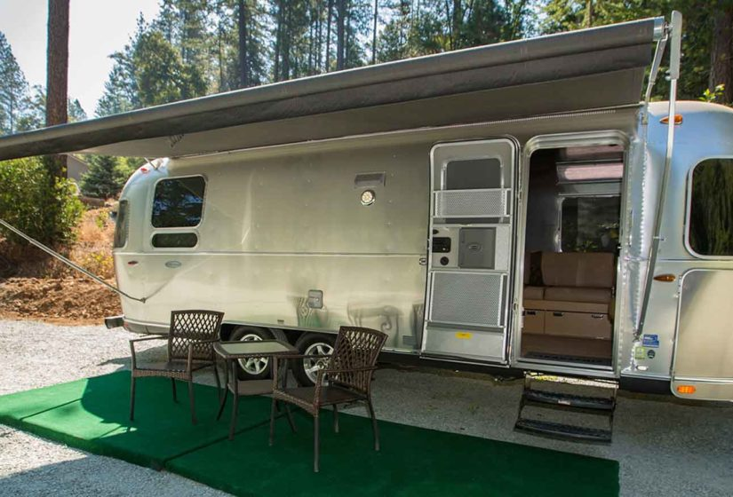 Exterior view of Windstream camper with canopy deployed over two paito chairs and table, with hill terrain in background accented by gazebo.