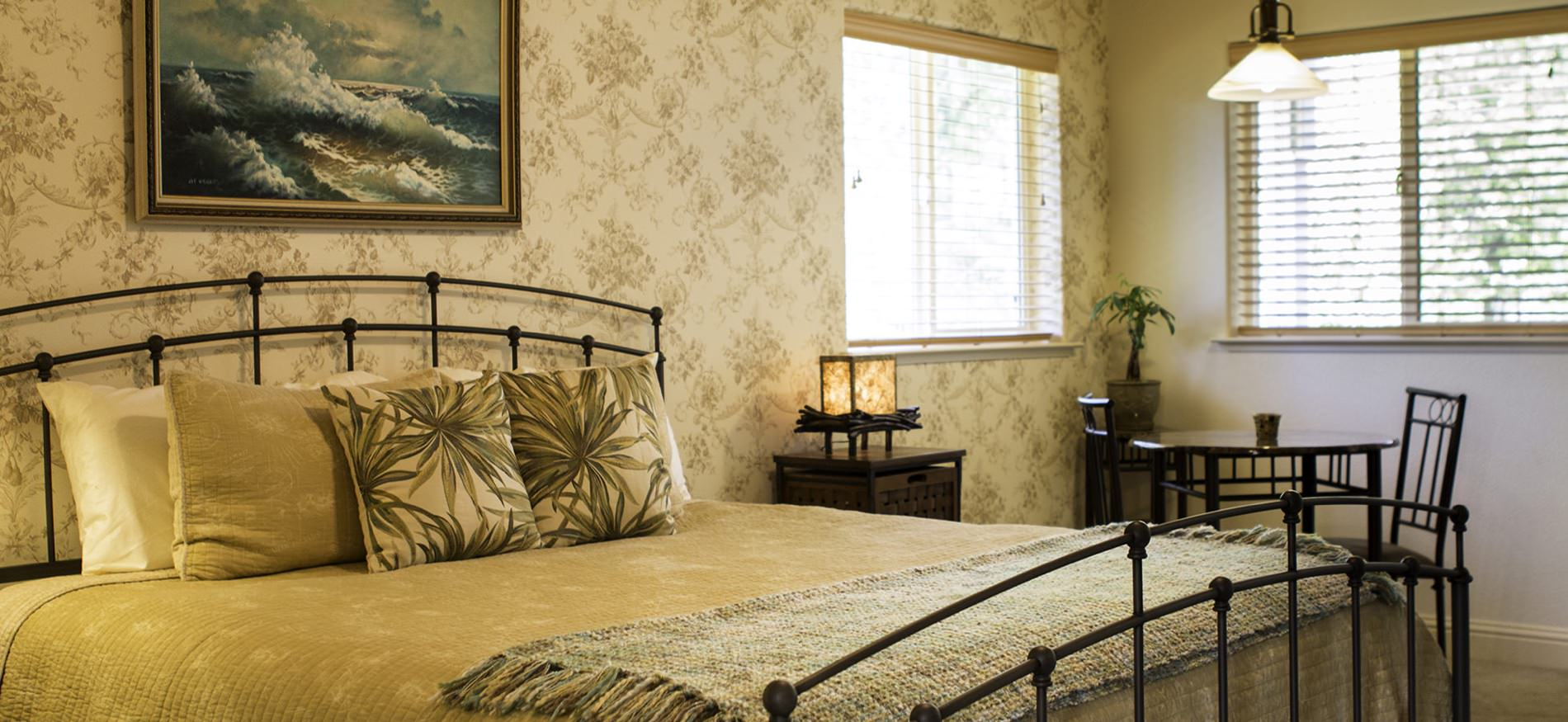 Bedroom with cream floral walls, dark metal bed with gold bedspread, nightstand with lamp and small table and chairs