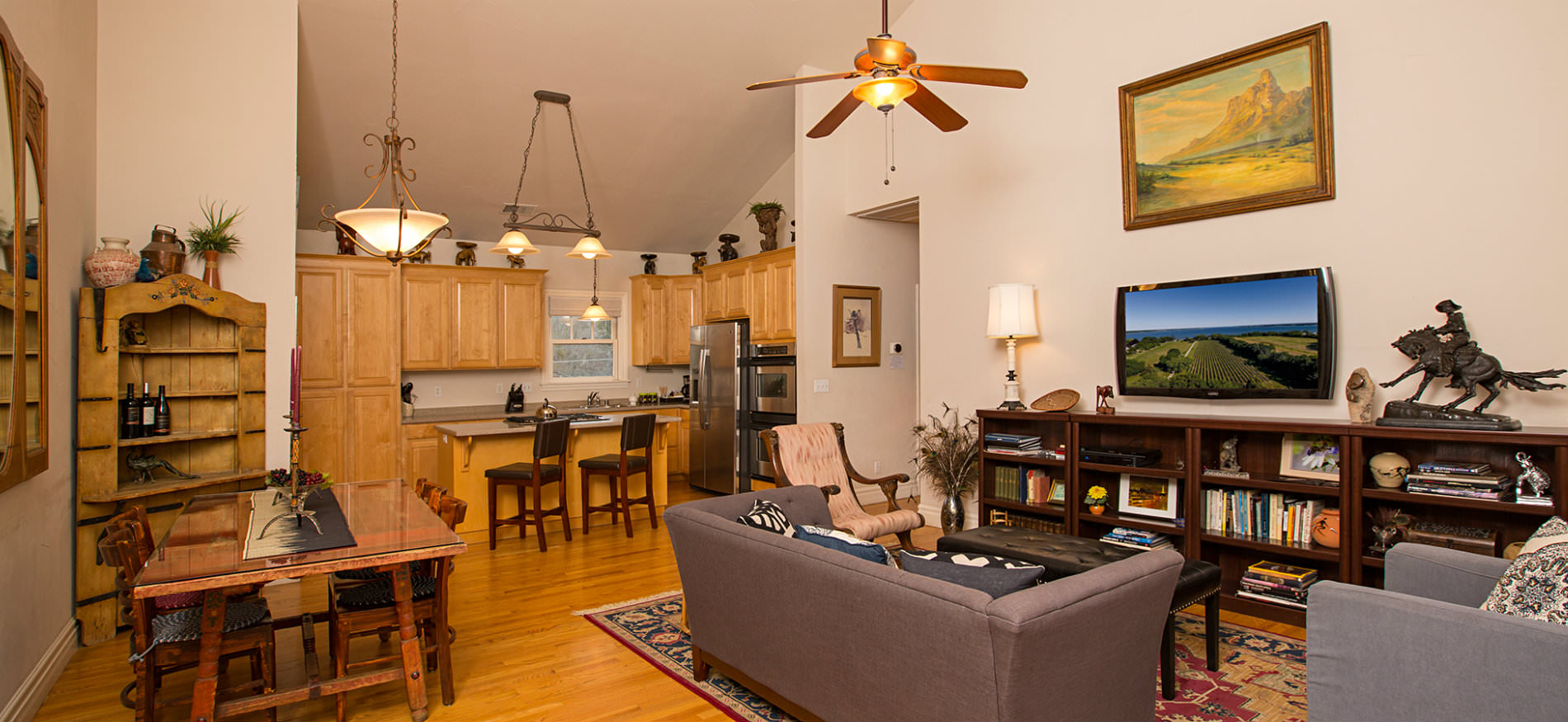 Vaulted room with light hardwood floors, sitting area with bookshelves and TV, dining table and kitchen with island seating