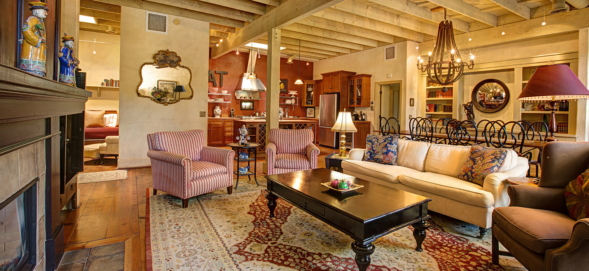 Open area with exposed ceiling beams, warm wood floors, rich wood kitchen cabinetry, and living area around a fireplace